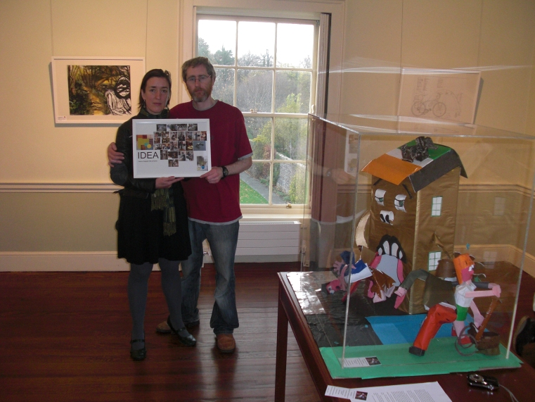 Jesse-James holding a work inspired by homeware giant Ikea. A House shaped falla, destined to be burned, inspired by the housing crisis and property bubble is seen in the foreground.